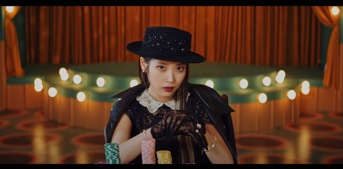 Screenshot of IU in the Coin music video. IU, dressed in classy clothes, at the end of the poker table with many poker chips in front of her. Behind her is an old-fashion stage (in which later in the video she sings on).